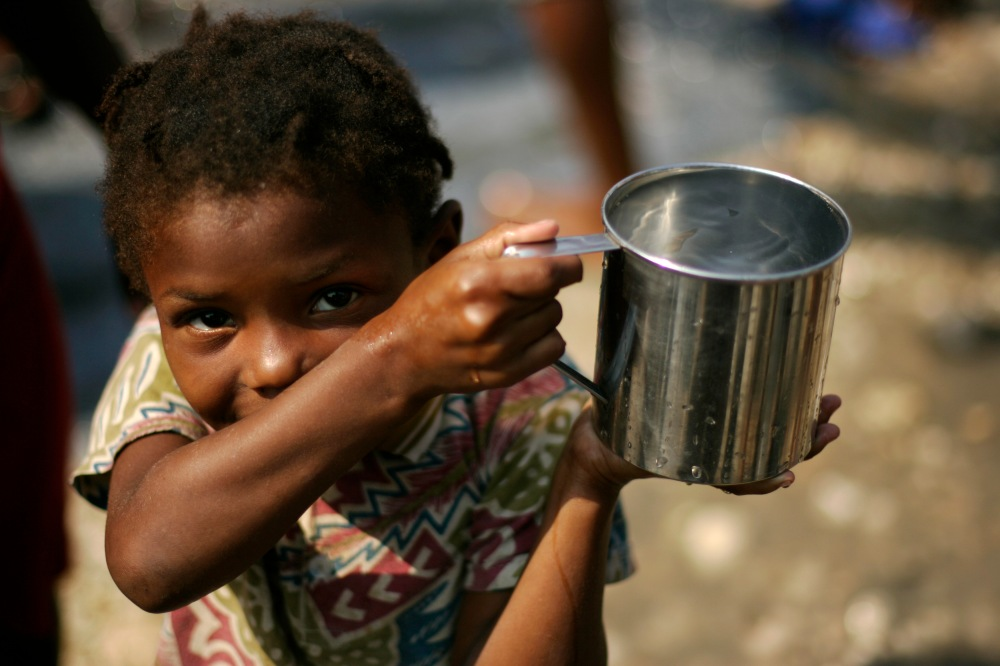 A girl carries a cup with non-potable water on a street in Port-au-Prince